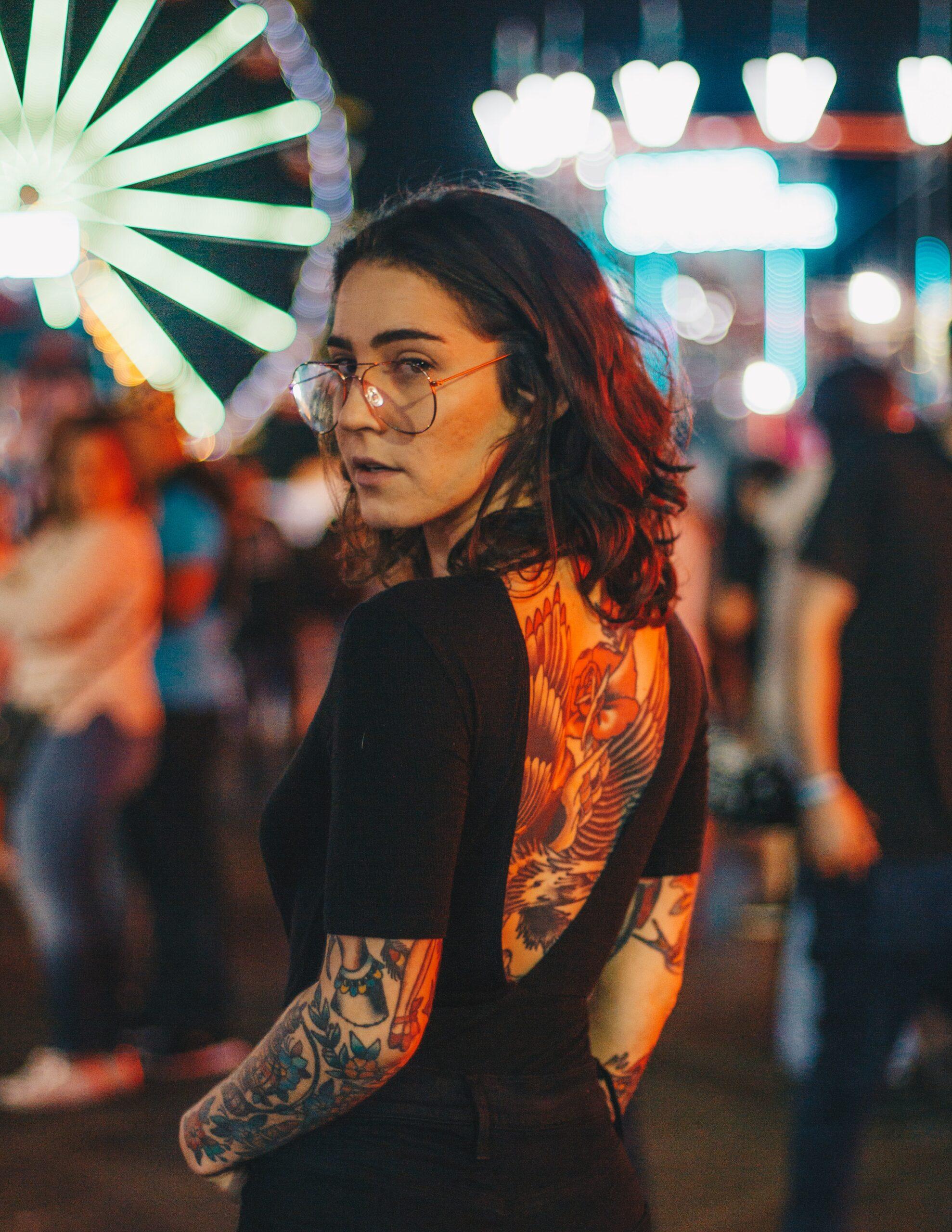 portrait photography of woman standing near Ferris Wheel