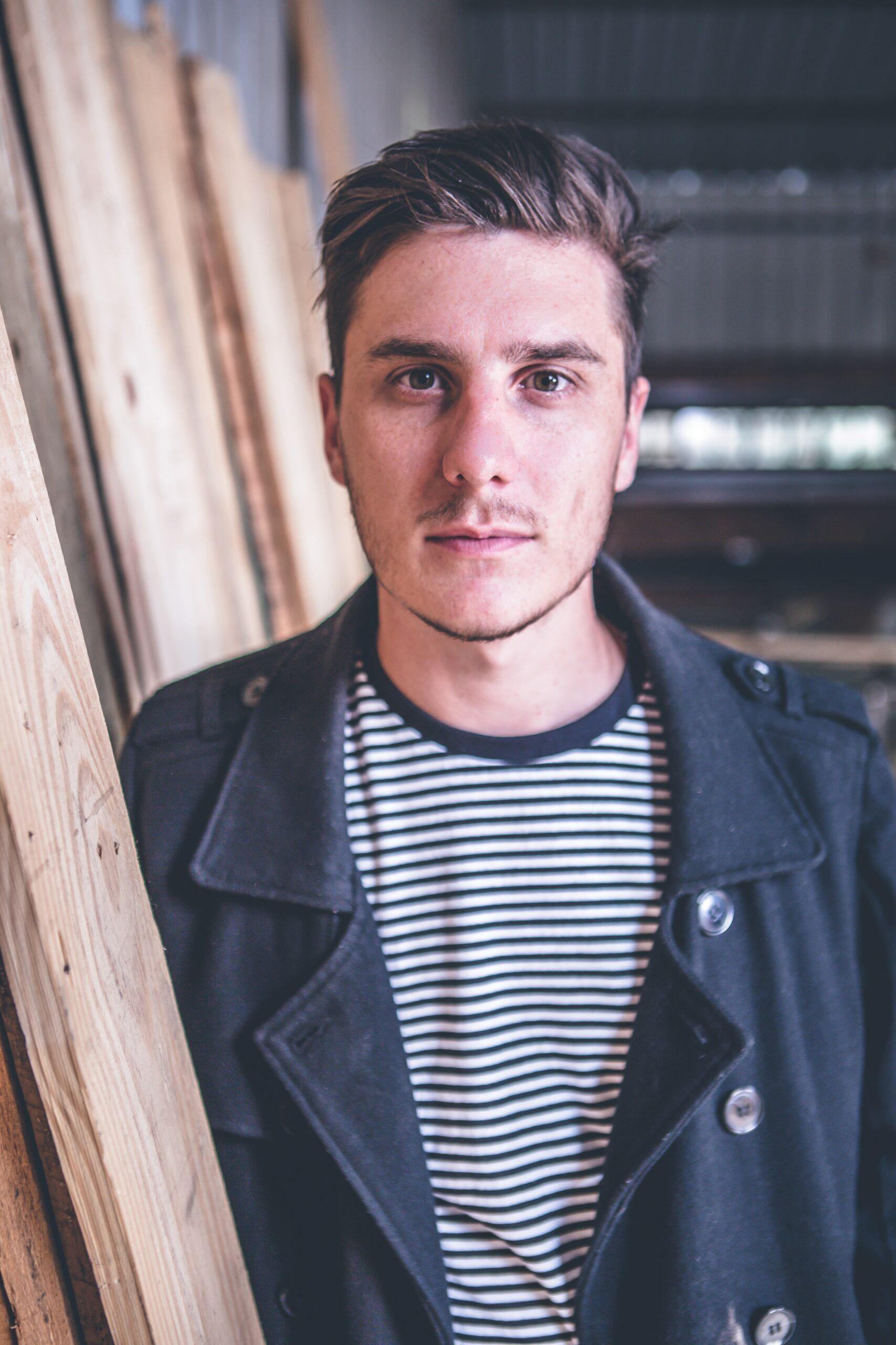 man standing beside wood planks