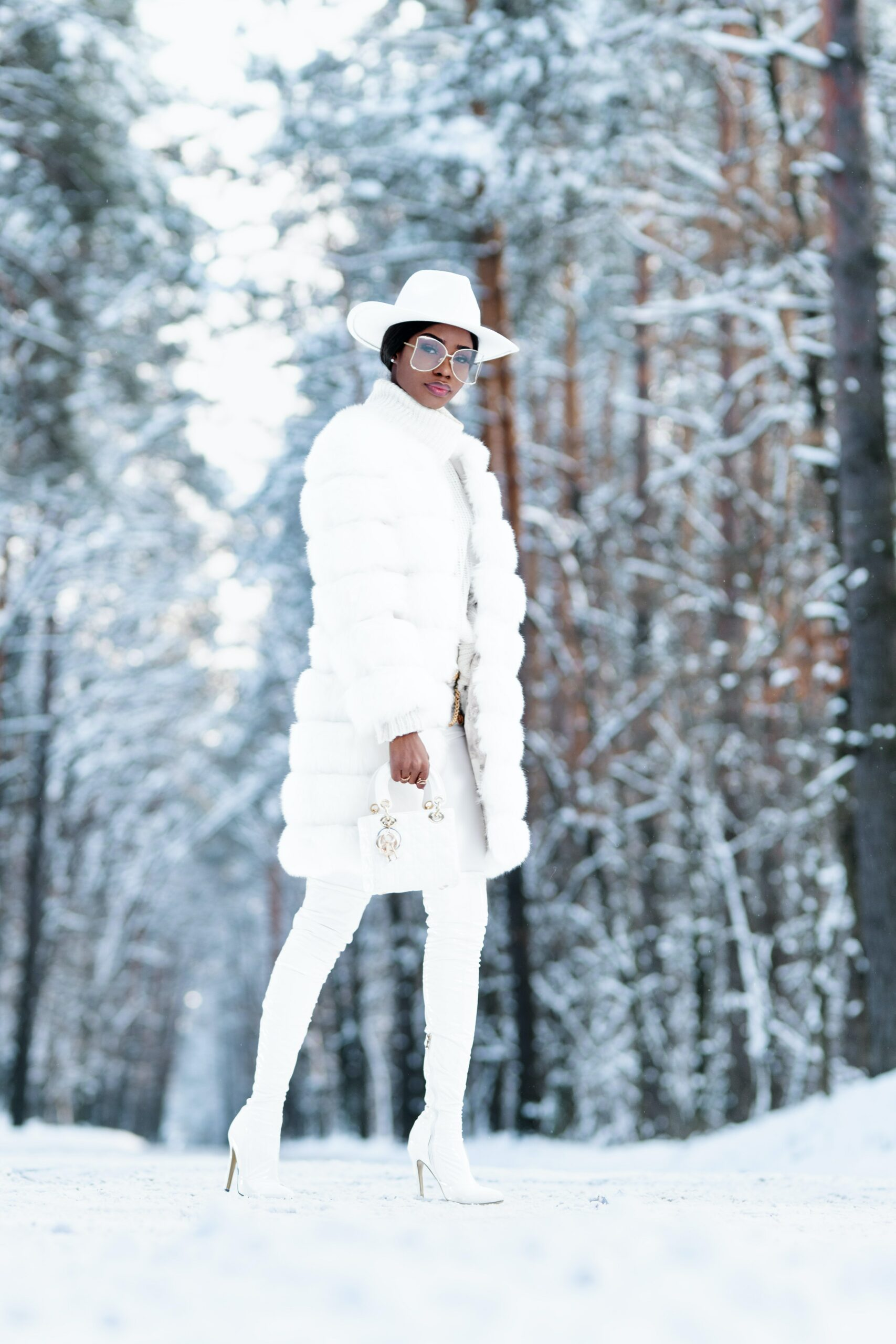 woman in white coat standing on snow covered ground during daytime